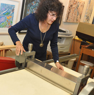 Marian Osher with the etching press. Photo by: Julie Hipkins.