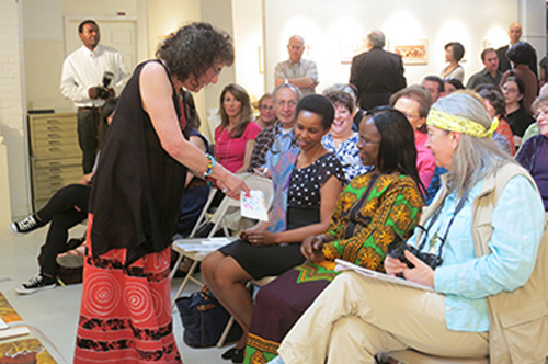 Marian Osher (left) talks with Ambassador Liberata Mulamula during her Jambo, Tanzania artist's demonstration. Photo by Anne McLaughlin.